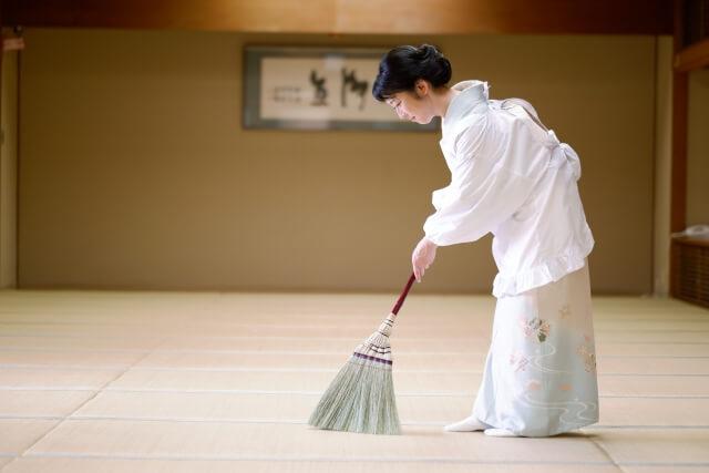 畳をほうきで掃除する女性