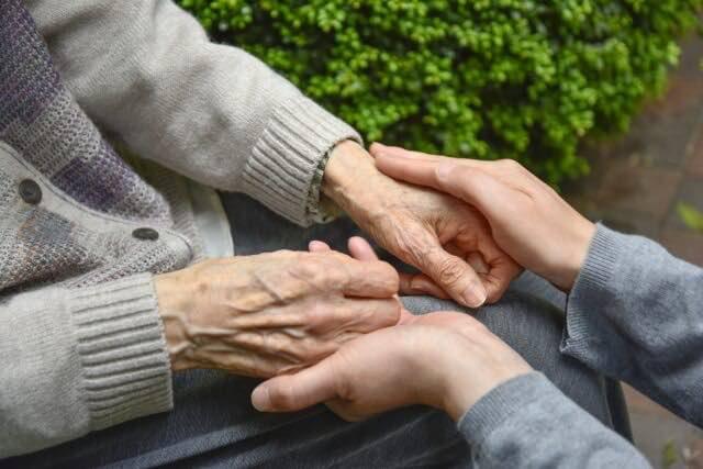 お年寄りの手を握りしめる手