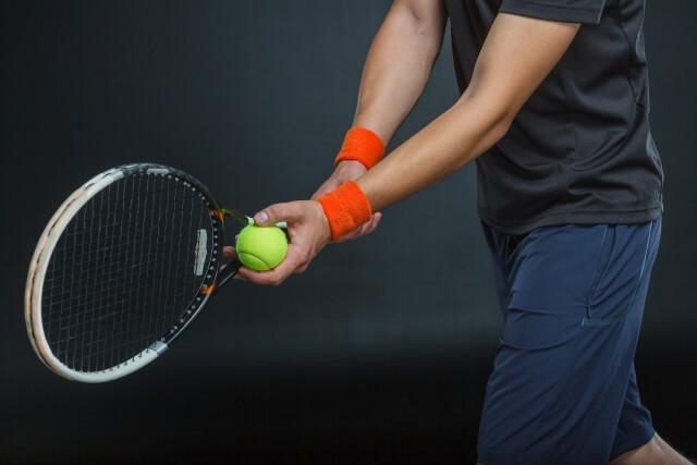テニスでサーブを打とうとする男性