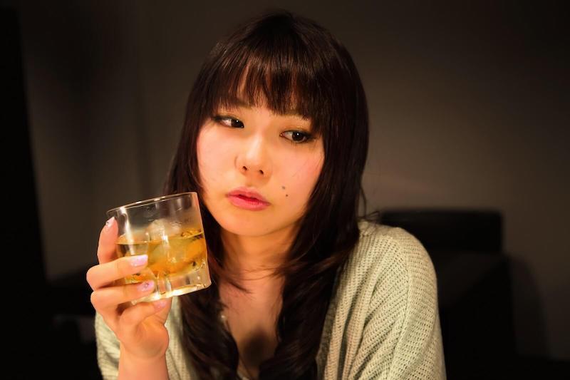 グラスで飲み物を飲む女性