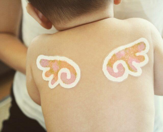 天使の羽がペイントされた赤ちゃんの背中