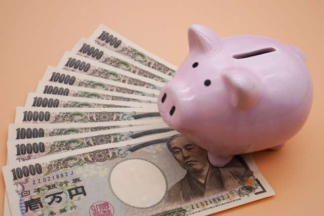 豚の貯金箱と複数の1万円札
