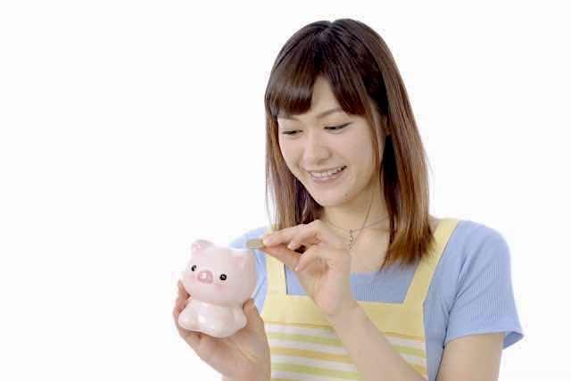 貯金箱にお金を入れる女性