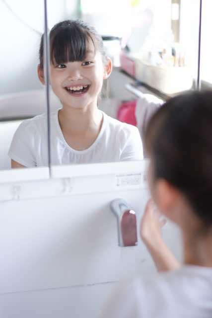 鏡に向かって笑顔の練習をする少女