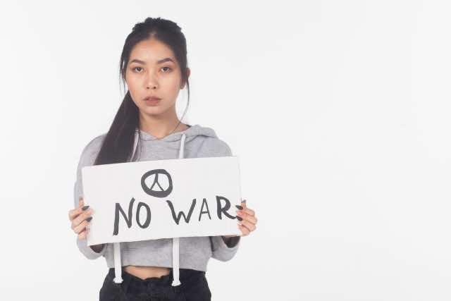 NO WARのプラカードを持つ女性