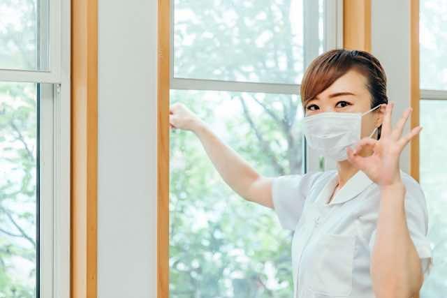 窓を換気する女性